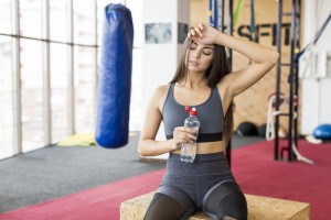 exhausted-woman-with-water-in-gym_23-2147778372